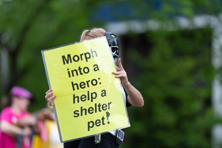 Louisville, Kentucky, USA - May 2, 2019: The Pegasus Parade, Woman holding a sign that says, Morph into a Hero: Help a shelter pet, promoting pet adoption during the parade