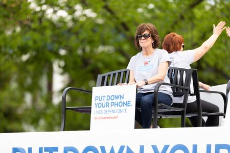 Louisville, Kentucky, USA - May 2, 2019: The Pegasus Parade, Woman holding a sign that says, put down your phone, lives depend on it, promoting driving safety