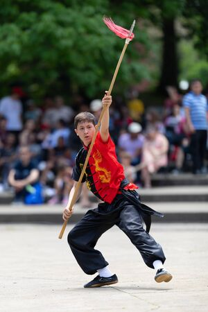Columbus, Ohio, USA - May 26, 2019: Columbus Asian Festival, Franklin Park, Boy wearing traditional chinese clothing handling a Kung Fu Spear. 報道画像