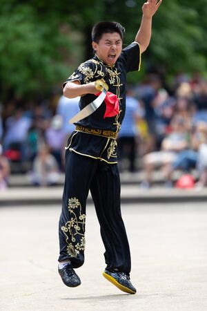 Columbus, Ohio, USA - May 26, 2019: Columbus Asian Festival, Franklin Park, Man wearing traditional chinese clothing handling a Kungfu broadsword during the festival 写真素材 - 130376753
