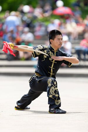 Columbus, Ohio, USA - May 26, 2019: Columbus Asian Festival, Franklin Park, Man wearing traditional chinese clothing handling a Kungfu broadsword during the festival 写真素材 - 130376761