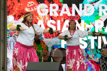 Grand Rapids, Michigan, USA - June 15, 2019: Asian Pacific Festival, Woman wearing traditional clothing performing a hula dance at the Rosa Parks Circle