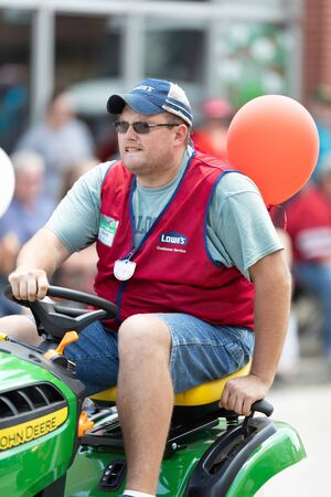 Buckhannon, West Virginia, USA - May 18, 2019: Strawberry Festival, Lowe's employee riding a John Deere Lawn mower, promoting Lowe's during the parade