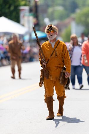 Buckhannon, West Virginia, USA - May 18, 2019: Strawberry Festival, Man wearing a colony era frontier costume, handling a musket during the parade 写真素材 - 129659789