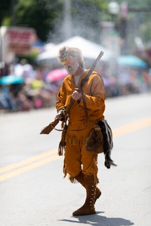 Buckhannon, West Virginia, USA - May 18, 2019: Strawberry Festival, Man wearing a colony era frontier costume, handling a musket during the parade 報道画像