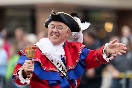 Holland, Michigan, USA - May 11, 2019: Tulip Time Parade, Man wearing traditional dutch clothing, handling a bell and waving at people during the parade