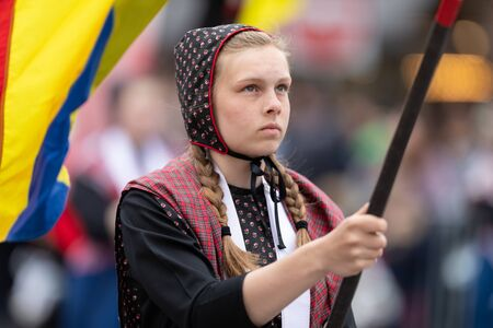 Holland, Michigan, USA - May 11, 2019: Tulip Time Parade, Young woman wearing traditional dutch clothing, carrying a flag down the street during the parade 에디토리얼