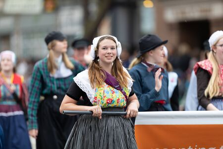 Holland, Michigan, USA - May 11, 2019: Tulip Time Parade, Young woman wearing traditional dutch clothing smiling, walking down the road during the parade