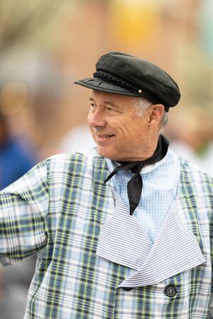 Holland, Michigan, USA - May 11, 2019: Tulip Time Parade, Man wearing traditional dutch clothing, smiling waving at people, going down the road during the parade