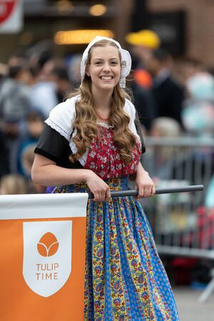 Holland, Michigan, USA - May 11, 2019: Tulip Time Parade, Woman smiles, wearing a traditional dutch outfit during the parade 에디토리얼