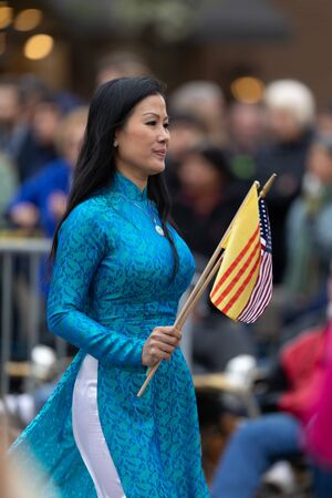 Holland, Michigan, USA - May 11, 2019: Tulip Time Parade, Vietnamese Woman wearing traditional clothing, carrying the American and vietnam flags