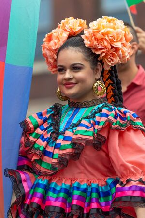 Chicago, Illinois, USA - September 8, 2019: 26th Street Mexican Independence Parade, Young woman wearing a traditional dress, with flowers on her head, smiling