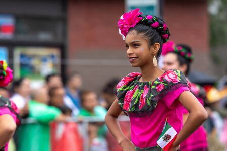 Chicago, Illinois, USA - September 8, 2019: 26th Street Mexican Independence Parade, Young mexican woman, wearing traditional clothing, smiling, holding the mexican flag, dancing