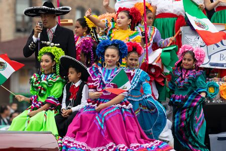 Chicago, Illinois, USA - September 8, 2019: 26th Street Mexican Independence Parade, Mexican girlsand boys, wearing traditional clothing, waving mexican flags on a float, during the parade