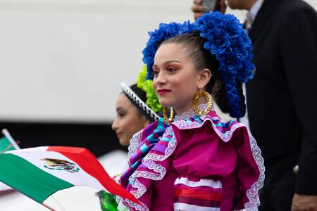 Chicago, Illinois, USA - September 8, 2019: 26th Street Mexican Independence Parade, Mexican girls, wearing traditional clothing, waving mexican flags on a float, during the parade