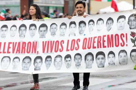 Chicago, Illinois, USA - September 8, 2019: 26th Street Mexican Independence Parade, Man and woman holding a banner with pictures of missing students in mexico, and it says, Alive they Took them, Alive we want them Editorial