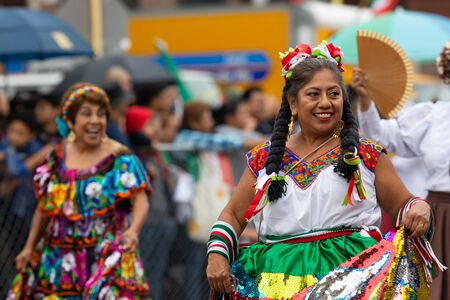 Chicago, Illinois, USA - September 8, 2019: 26th Street Mexican Independence Parade, Mexican woman wearing traditional clothing, smiling during the parade Editorial