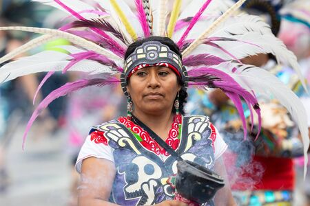 Chicago, Illinois, USA - September 8, 2019: 26th Street Mexican Independence Parade, mexican woman wearing traditional aztec clothing during the parade