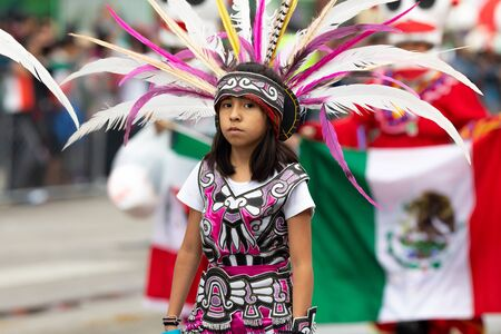 Chicago, Illinois, USA - September 8, 2019: 26th Street Mexican Independence Parade, young girl wearing aztec clothing, with the mexican flag on her back, stares at the camera