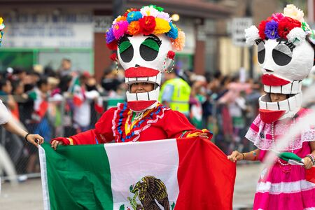 Chicago, Illinois, USA - September 8, 2019: 26th Street Mexican Independence Parade, women wearing traditional clothing, with a skull mask, carrying the mexican flag