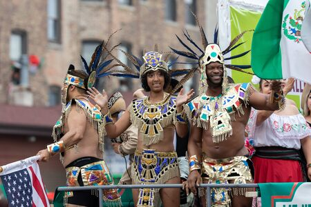 Chicago, Illinois, USA - September 8, 2019: 26th Street Mexican Independence Parade, African american,  waring an aztec outfit, waving the mexican flag, on a float