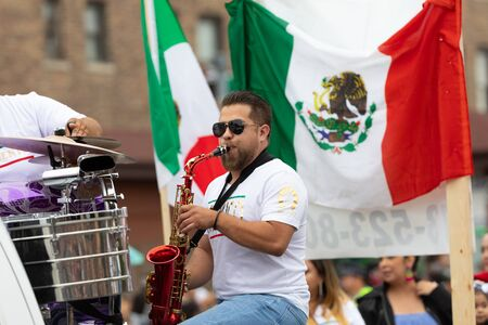 Chicago, Illinois, USA - September 8, 2019: 26th Street Mexican Independence Parade, Man playing the Saxophone, with the Mexican flag at his back during the parade