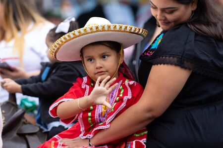Chicago, Illinois, USA - September 8, 2019: 26th Street Mexican Independence Parade, girl on her mothers arms, wearing traditional clothing with a sombrero, waving at the spectators