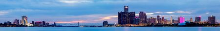 The Border Cities of Detroit, Michigan, United States of America, and Windsor, Ontario Province, Canada, connected by the Ambassador Bridge as seen from the Detroit River at Sunset Stock Photo