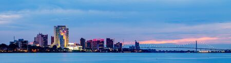 Windsor city in the Canadian Province of Ontario, Canada, with the Ambassador Bridge on the background, as seen from the Detroit River at Sunset