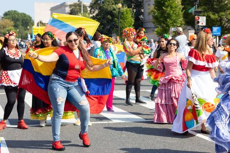 Washington DC, USA - September 21, 2019: The Fiesta DC, Colombian woman holding her national flag dancing during the parade
