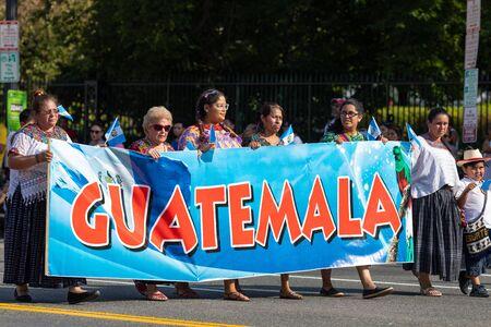 Washington DC, USA - September 21, 2019: The Fiesta DC, Guatemalan women wearing traditional clothing, carry a large banner that says Guatemala