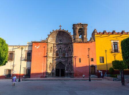 San Miguel de Allende, Guanajuato, Mexico - Nov 25, 2019: Locals walking along the Templo de Nuestra Señora de La Salud, early in the day