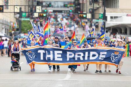 Cincinnati, Ohio, USA - June 22, 2019: The Cincinnati Pride Parade, people waving rainbow flags, and carrying banner promoting FC Cincinnati Éditoriale