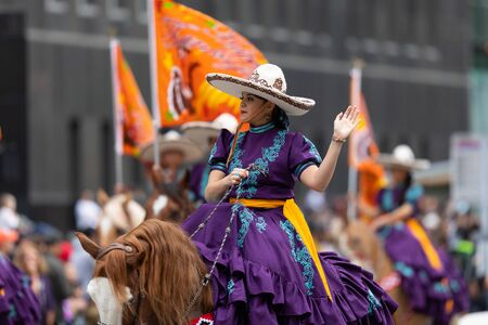 Houston, Texas, USA - November 28, 2019: H-E-B Thanksgiving Day Parade, A group of charro horse riders carrying the texas flag and flags conmemorating Thanksgiving