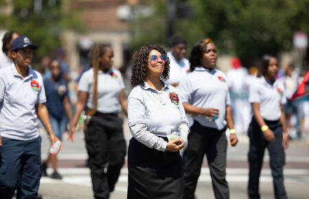 Chicago, Illinois, USA - August 8, 2019: The Bud Billiken Parade, Members of the fire brigade, marching down MLK street at the parade