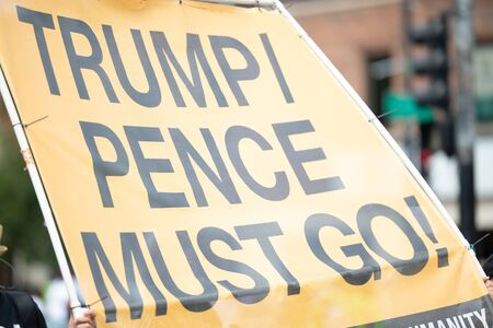 Chicago, Illinois, USA - August 8, 2019: The Bud Billiken Parade, People holding a sign that says Trump, Pence must Go