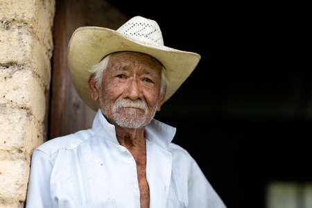 El Chorrito, Tamaulipas, Mexico, July 2, 2019: Mexican Senior, at his adobe home, waits by his door
