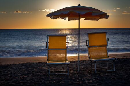idling: Backlight on the sea, umbrellas and deck chairs from Marina di Bibbona, Tuscany