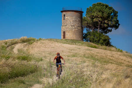 footwork: Bibbona, Tuscany, Italy - May 24, 2016: lifestyle using the mountain bike to ride in the paths of Tuscany, on background the old mill and of the protected natural area of the Macchia Magona