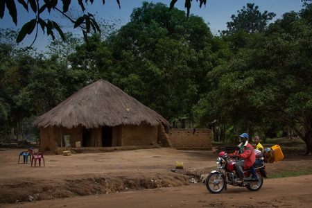 developing country: Yongoro, Sierra Leone - June 03, 2013: West Africa, the village of Yongoro in front of Freetown, a family through the village with their own motorcycle