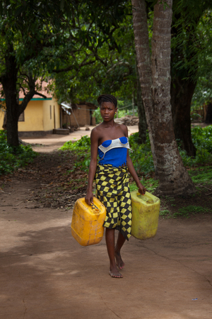 developing country: Yongoro, Sierra Leone - June 03, 2013: West Africa, the village of Yongoro in front of Freetown, girl carries water cans from artesian well
