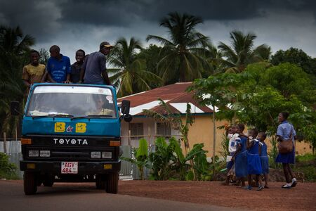 intersect: Makeni, Sierra Leone, Africa - June 06, 2013: Makeni, Bombali District North of Sierra Leone, trucks carrying workers intersect children out of school