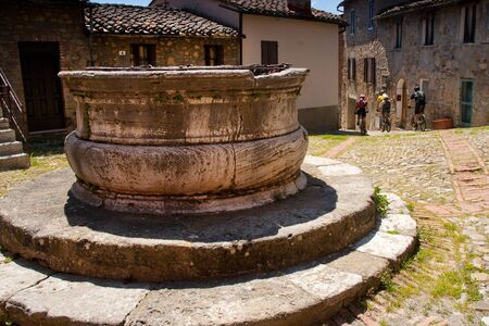 Val dOrcia, Siena, mountain bike excursion in the Tuscan hills - Piazza della Vecchietta with the well and the medieval palace, Rocca dOrcia Stock Photo