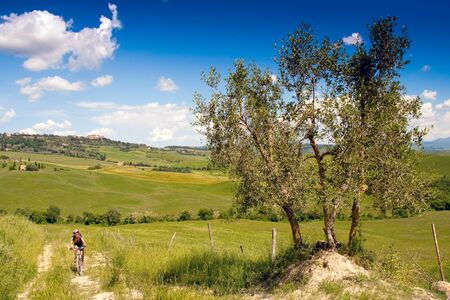 Val dOrcia, Siena, mountain bike excursion in the Tuscan hills - challenging climb on background Pienza