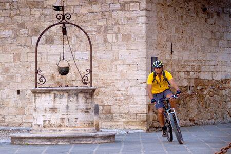 san quirico d'orcia: Val dOrcia, Siena, mountain bike excursion in the Tuscan hills - passage from the Collegiate Church, San Quirico dOrcia Stock Photo
