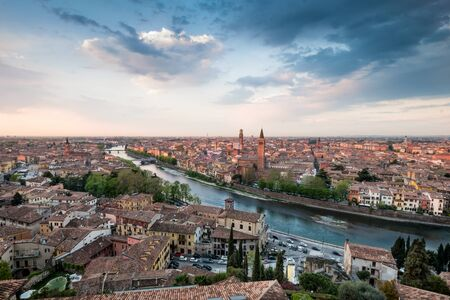 Verona skyline with river Adige, bridges, Santa Anastasia Church and Torre dei Lamberti or Lamberti Tower at dawn view from Castel San Pietro, Italy