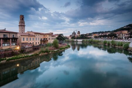 mediterranean culture: Verona, Italy - Ancient Roman bridge Ponte Pietra and the River Adige, Duomo tower in background, Verona, Italy Stock Photo