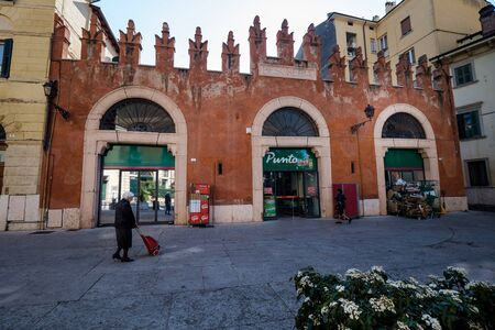 VERONA, Italy - April 04, 2017: old woman walking to the market early morning in Piazzetta Pescheria