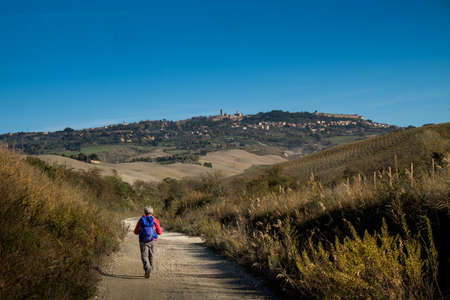 Hikers depart from Saline for the Volterra hills with panoramic views across the old railway Stock Photo