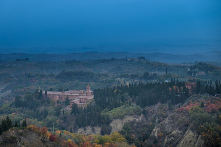 Monte Oliveto Maggiore, Siena, Tuscany - Novembre 12, 2017: Autumnal trekking in the province of Siena, from Buonconvento village along the Cassia Road, to the confluence of the rivers Arbia and Ombrone then along the historical Via Francigena and the village of Chiusure we got the Monte Oliveto Maggiore Abbey 版權商用圖片